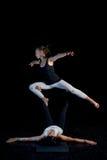 Dos muchachas que realizan actitudes de la acro-yoga Foto de archivo libre de regalías