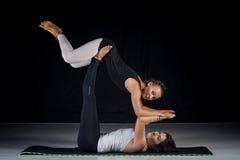 Dos muchachas que realizan actitudes de la acro-yoga Fotos de archivo