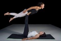Dos muchachas que realizan actitudes de la acro-yoga Foto de archivo