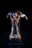 Dos muchachas que realizan actitudes de la acro-yoga Imagenes de archivo