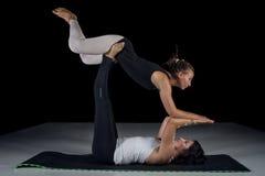 Dos muchachas que realizan actitudes de la acro-yoga Fotos de archivo libres de regalías