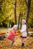 Dos muchachas que saltan en parque del otoño Imagen de archivo libre de regalías