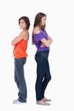 Dos muchachas que se colocan de nuevo a la parte posterior Imagen de archivo libre de regalías