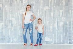 Dos muchachas que se colocan en la pared gris Fotografía de archivo libre de regalías