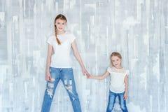 Dos muchachas que se colocan en la pared gris Imágenes de archivo libres de regalías