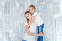 Dos muchachas que se colocan en la pared gris Imagen de archivo libre de regalías