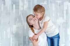 Dos muchachas que se colocan en la pared gris Fotos de archivo libres de regalías