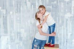 Dos muchachas que se colocan en la pared gris Foto de archivo libre de regalías