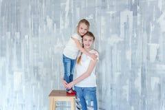 Dos muchachas que se colocan en la pared gris Fotos de archivo