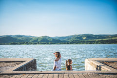 Dos muchachas que se colocan en muelle del río y que miran de lado Foto de archivo libre de regalías