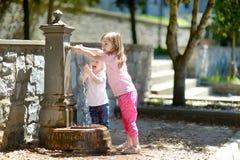 Dos muchachas que se divierten con la fuente del agua potable foto de archivo libre de regalías