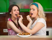 Dos muchachas que se divierten con las galletas en la cocina Imagen de archivo libre de regalías