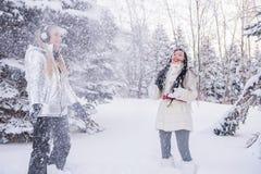 Dos muchachas que se divierten en la nieve entre los árboles La atmósfera de la diversión y de la relajación del invierno imágenes de archivo libres de regalías