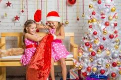 Dos muchachas que se divierten que intenta desatar el bolso con los regalos Foto de archivo
