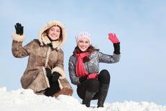 Dos muchachas que se ponen en cuclillas en el uno-brazo de la nieve y del waff Fotografía de archivo