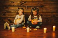Dos muchachas que se preparan para el día de fiesta Noche, velas, calabaza, cuentos Fotos de archivo