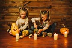 Dos muchachas que se preparan para el día de fiesta Noche, velas, calabaza, cuentos Imagen de archivo libre de regalías