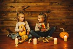 Dos muchachas que se preparan para el día de fiesta Noche, velas, calabaza, cuentos Fotografía de archivo