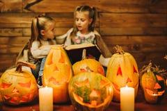 Dos muchachas que se preparan para el día de fiesta Noche, velas, calabaza, cuentos Imagenes de archivo