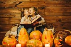 Dos muchachas que se preparan para el día de fiesta Noche, velas, calabaza, cuentos Fotografía de archivo libre de regalías