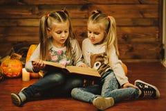 Dos muchachas que se preparan para el día de fiesta Noche, velas, calabaza, cuentos Imágenes de archivo libres de regalías