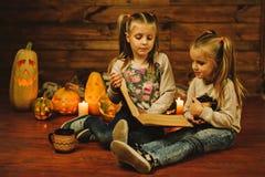 Dos muchachas que se preparan para el día de fiesta Noche, velas, calabaza, cuentos Imagen de archivo