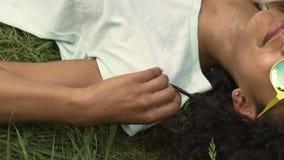 Dos muchachas que se relajan en hierba, la reflexión del cielo en gafas de sol, la amistad y la diversión almacen de video