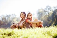 Dos muchachas que se sientan de nuevo a la parte posterior Imagen de archivo