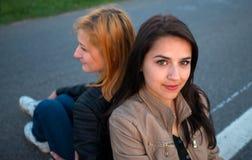 Dos muchachas que se sientan de nuevo a la parte posterior Fotos de archivo