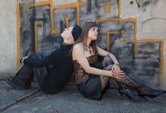 Dos muchachas que se sientan delante de la pared de la pintada Imágenes de archivo libres de regalías