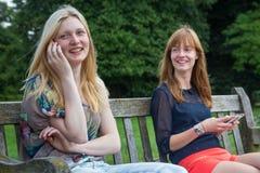Dos muchachas que se sientan en banco en parque con el móvil Foto de archivo libre de regalías