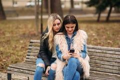 Dos muchachas que se sientan en el banco al aire libre Imagen de archivo libre de regalías