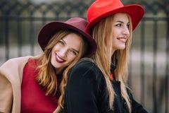 Dos muchachas que se sientan en el banco y la sonrisa Imagenes de archivo