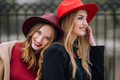 Dos muchachas que se sientan en el banco y la sonrisa Fotografía de archivo