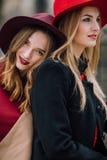 Dos muchachas que se sientan en el banco y la sonrisa Fotos de archivo libres de regalías