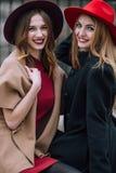 Dos muchachas que se sientan en el banco y la sonrisa Imágenes de archivo libres de regalías