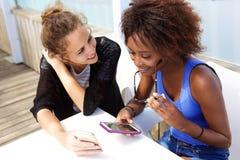 Dos muchachas que se sientan en el café con los teléfonos móviles Fotos de archivo