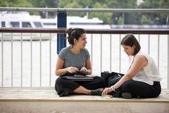 Dos muchachas que se sientan en el pavimento del banco del sur del Támesis Imágenes de archivo libres de regalías