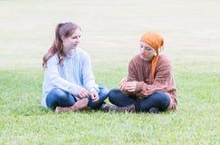 Dos muchachas que se sientan en hierba Fotografía de archivo libre de regalías