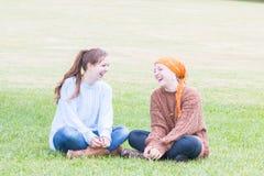 Dos muchachas que se sientan en hierba Foto de archivo libre de regalías