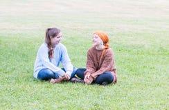 Dos muchachas que se sientan en hierba Imagen de archivo libre de regalías