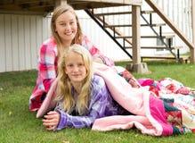 Dos muchachas que se sientan en la hierba Fotografía de archivo