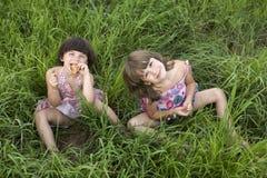 Dos muchachas que se sientan en la hierba Imagen de archivo libre de regalías
