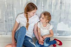 Dos muchachas que se sientan en la pared gris Imagen de archivo libre de regalías