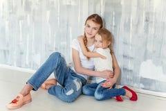 Dos muchachas que se sientan en la pared gris Foto de archivo