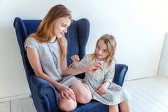 Dos muchachas que se sientan en silla azul moderna Imágenes de archivo libres de regalías