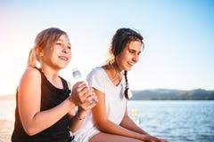 Dos muchachas que se sientan por el mar y que ríen junto Foto de archivo