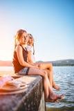 Dos muchachas que se sientan por el mar y que ríen junto Imágenes de archivo libres de regalías