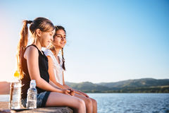 Dos muchachas que se sientan por el mar y que ríen junto Imagen de archivo libre de regalías