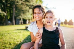 Dos muchachas que sonríen junto en un parque Fotos de archivo